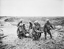 Several British soldiers, knee deep in mud, carry a wounded comrade on a stretcher.