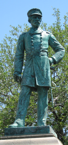 Standing figure of Admiral Raphael Semmes. He wears confederate attire, including a long coat which extends to his knees, and a cap on his head. His left arm is bent so that his fist rests on his hip, with sword hanging immediately behind. His right arm is at his side with binoculars in his hand. Erected in 1899, the bronze aged to deep green long ago like the Statue of Liberté in New York. The base features three bronze plaques, including one which depicts the C.S.S. Alabama at sea.
