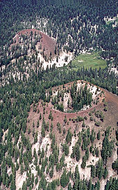 Two red cinder cones in a forest. There is a meadow at the base of one of the ones