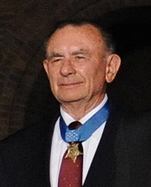 Head of a smiling white man wearing a suit, red tie, and a medal hanging from a blue ribbon around his neck