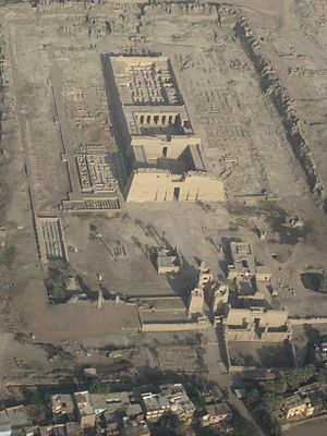 Rectangular stone building from above, with courtyards and pylons at the front and the remains of walls at the back. A rectangular wall and the foundations of other buildings surround the main building.