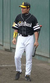 "Arihito Muramatsu wearing a black baseball uniform with ""SoftBank"" across the chest in white script standing and holding a baseball bat"