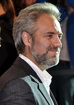 Profile of a grey haired, bearded man smiling as he faces to the right. He wears an unbuttoned white shirt accompanied with a grey suit.