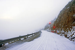 A snow-covered road next to a rocky cliff face on the right with only fog visible on the left. Ahead is a temporary traffic light showing red.