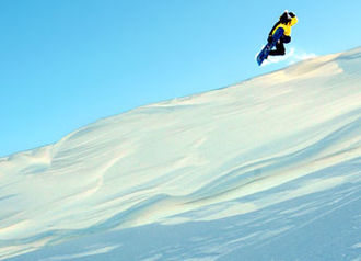 Extreme sport - Snowboarder drops off a cornice.