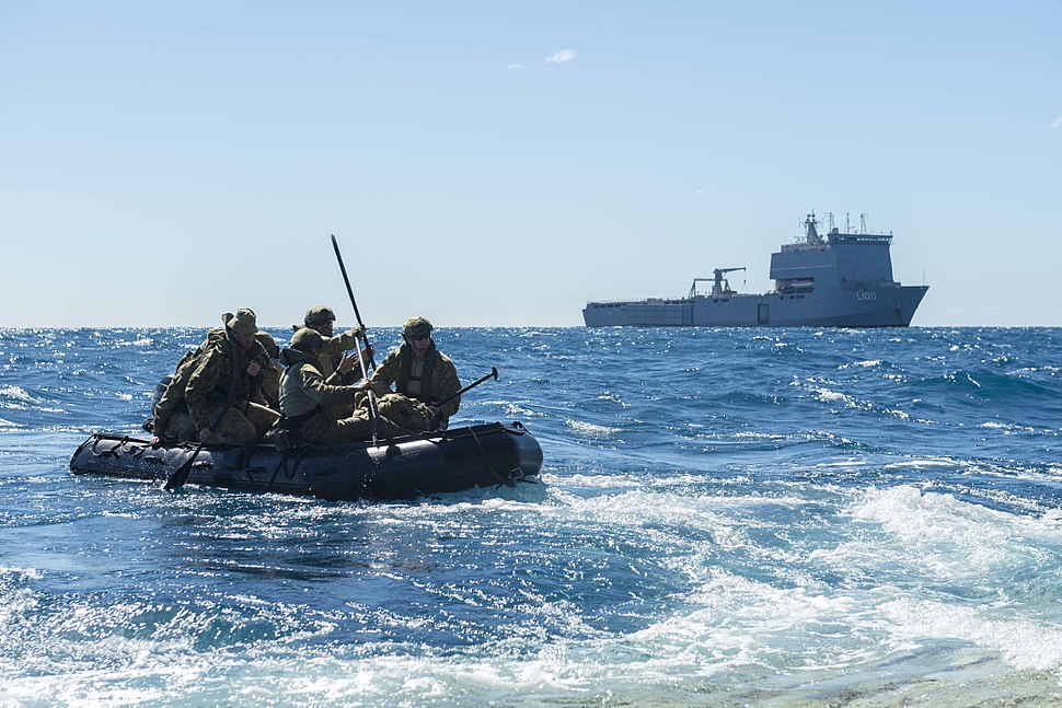 Soldiers assigned to 2nd Battalion, Royal Australian Regiment in a combat rubber raiding craft with HMAS Choules in the background
