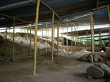 A cleared area of bare soil strewn with rubble, with raised areas to the left and right and roofed with corrugated metal supported by timber poles