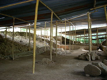 A cleared area of dirt strewn with rubble, with raised areas to the left and right and covered by a roof supported by wooden poles.