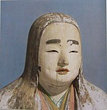 Head and shoulder portrait of a female statue with long hair, painted eyebrows, colored lips and cloths.