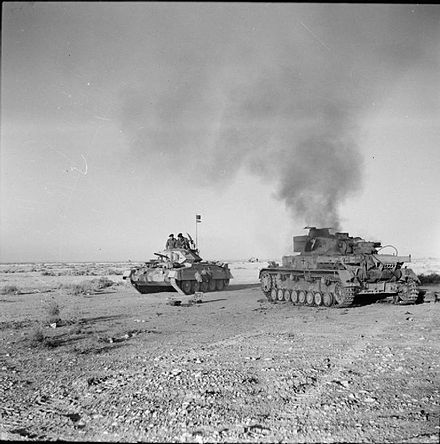 A Crusader tank passes a burning German PzKpfw IV tank, 27 November 1941. The British Army in North Africa 1941 E6752.jpg
