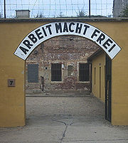 Photographie en couleurs de l'entrée du camp de concentration de Theresienstadt surmontée par l'inscription Arbeit macht frei