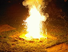 A photo of a white flame from which smoke rises and slightly bluish, otherwise also white sparks fly.  The flame rises from a flat cone of earth, is about 30 centimeters high and illuminates the grass around the cone.