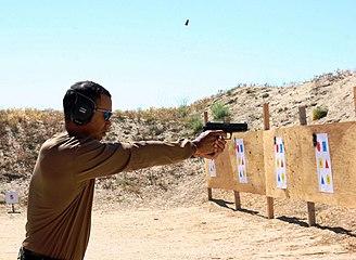 Un homme tenant une arme à la main dans le désert.