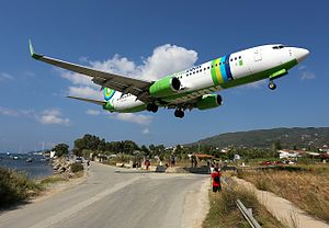 Skiathos International Airport - A Boeing 737-800 coming in to land above a group of planespotters at Skiathos.