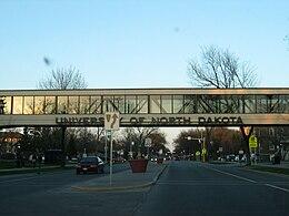 "A road facing a bridge that prominently displays ""University of North Dakota"