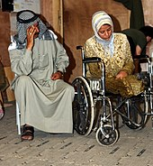 woman seated in a wheelchair with military personnel in background