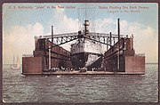 picture of a large battleship from rear inside a giant floating box-like structure in a harbor