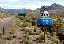 "White sign in foreground saying ""South US 395"" and green sign in background giving distances to June Lake, Mammoth Lakes and Los Angeles."