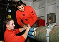 US Navy 050516-N-2515C-020 Aviation Ordnanceman 3rd Class Chris Zimmerman and Aviation Ordnanceman 3rd Class James Serrato install a WDU-4A-A inert air-launched 2.75-Inch rocket into a rocket pod aboard the amphibious assault s.jpg