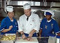 US Navy 050525-N-1941M-001 Culinary Specialist 2nd Class Michelle Harvey, left, and Culinary Specialist 3rd Class Tawny A. Cortezparedes learn culinary tips from Chef Samuel Glass aboard the amphibious assault ship USS Tarawa (.jpg