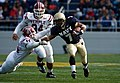 US Navy 061118-N-0696M-152 Naval Academy Midshipmen running back Reggie Campbell stiff-arms Temple University Owls linebacker Walter Mebane at Navy-Marine Corps Memorial Stadium.jpg