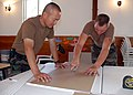 US Navy 070911-N-8547M-044 Lt. Song Hwang, chaplain of Naval Mobile Construction Battalion (NMCB) 5, left, and Builder Constructionman Robert L. Dynda, of the battalion's air detachment, cut sheetrock during a constructio.jpg
