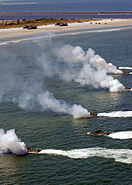 US Navy 090425-N-4879G-393 A group of multinational amphibious assault vehicles from the amphibious dock landing ship USS Ashland (LSD 48) deploy smoke to cover their landing during a simulated amphibious landing demonstration
