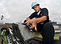 US Navy 090805-N-5386R-037 Aviation Boatswain's Mate (Equipment) Airman Ignacio Arbildi, from Las Vegas, sands a catapult boot aboard the aircraft carrier USS Abraham Lincoln (CVN 72).jpg