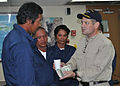 US Navy 100714-N-XXXXT-348 Capt. James Driver offers water and cash donated by the ship's crew to a group of Filipino fishermen rescued from sea after nine hours in the water.jpg