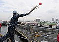 US Navy 111102-N-WJ771-084 Seaman Recruit Travis N. Abankwah throws a heaving line from the forecastle of the forward-deployed amphibious dock land.jpg