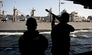 US Navy 111221-N-OY799-077 Gunner's Mate 3rd Class Cody Adams, right, fires a messenger line to the Military Sealift Command fast combat support sh.jpg
