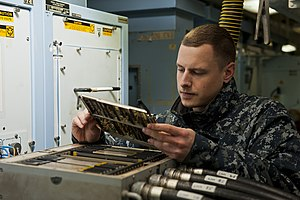 US Navy 120112-N-BT887-190 Aviation Electronics Technician Airman Michael Minten, from Little Chute, Wis., performs maintenance on a roll, pitch, a.jpg