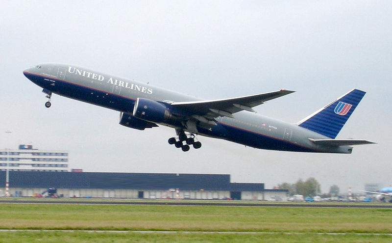 Airliner takeoff. The jet's nose is angled upwards as it lifts above the runway, with landing gear still deployed.