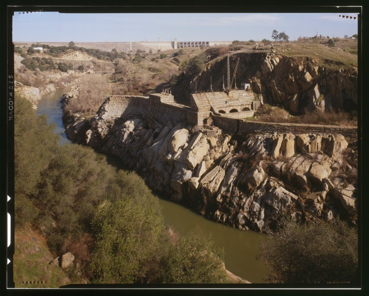 VIEW OF AMERICAN RIVER, SHOWING REMAINS OF OLD FOLSOM DAM, HEADGATES AND CANAL. NEW FOLSOM DAM IS IN THE BACKGROUND - Folsom Powerhouse, Adjacent to American River, HAER CAL,34-FOLSO.V,2-95 (CT)