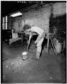VIEW OF WORKMAN WITH MOLTEN BRASS IN CRUCIBLE - Bevin Brothers Bell Shops, Bevin Court, East Hampton, Middlesex County, CT HAER CONN,4-HAMPE,1-8.tif