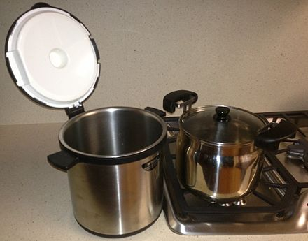 A vacuum flask cooker with the inner pot on a kitchen stove