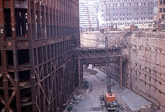 World Trade Center station (PATH) - Looking northeast. The frame of the South Tower is on the left. PATH eastbound tunnel F can be seen in the center, penetrating the slurry wall on its way up Cortlandt Street to Hudson Terminal. The slurry wall runs along the west side of Greenwich Street. The IRT subway tunnel runs below the street (behind the slurry wall).
