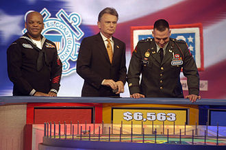 Game show - U.S. military servicemen participate in television game show Wheel of Fortune with host Pat Sajak.