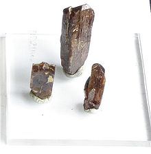 Three column shaped brown crystals on a white background