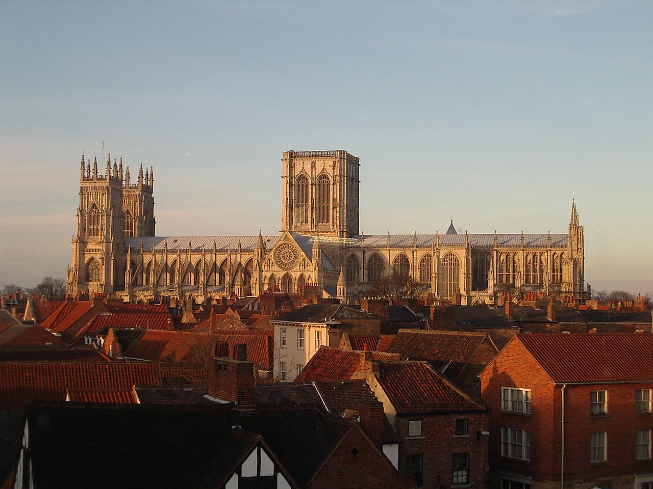 York Minster seen from the side - a long building with a pair of towers at one end and a massive central tower with two perpendicular windows. The round rose window can be seen on the south transcept.