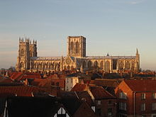 York Minster seen from the side - a long building with a pair of towers at one end and a massive central tower with two perpendicular windows. The round rose window can be seen on the south transept.