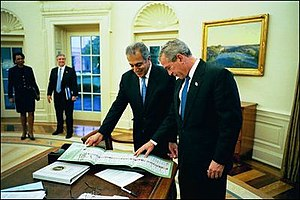 Afghan Americans - Zalmay Khalilzad presents George W. Bush an Afghan ballot from the 2004 presidential election in Afghanistan.