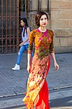 Printed Ao dai in front, Western outfit in the background.