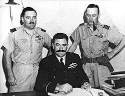 Half length portrait of three military men behind a desk, all with pilot's wings on left breast pocket. One of the men, seated, has a large dark moustache and is wearing a dark winter uniform. The other two, standing on either side of the seated figure, wear short-sleeved tropical uniforms; one of them has a small moustache, the other has a holster on his belt and is clean-shaven and smoking a pipe