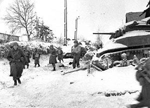 "30th Infantry Division (United States) - Men of the 117th Infantry Regiment, part of the 30th Infantry Division, move past a destroyed American M5 ""Stuart"" tank on their march to capture the town of St. Vith at the close of the Battle of the Bulge, January 1945."