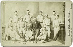 Twelve members of a baseball team are posing for a photograph, consisting of three rows; five men standing, four sitting in a chair or bench, and three sitting on the floor