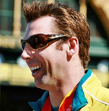 Profile of a smiling, brown haired young main, wearing sunglasses, wearing a yellow jacket tracksuit with a green collar, with a red medal ribbon around his neck.
