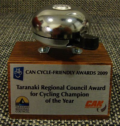 2009 award trophy: a wooden block bearing a plaque, and a bicycle bell mounted on top of the block