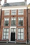foto van Pand met verdieping, mezzaninoverdieping en omlijste ingang onder dwarskap met hoekschoorstenen