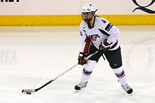 "A female ice hockey player, wearing a white jersey with a stylized ""USA"" on the chest, has the puck and is looking forward, either for a shot or a teammate to pass to."